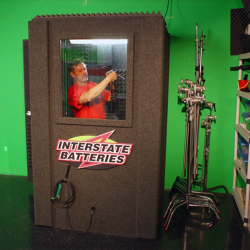 A man doing product testing for Interstate Battery inside of a WhisperRoom