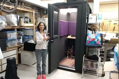 A woman standing next to a WhisperRoom in her garage