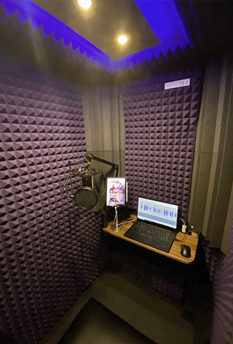 Interior of WhisperRoom with purple foam, a desk, a computer, and recording equipment