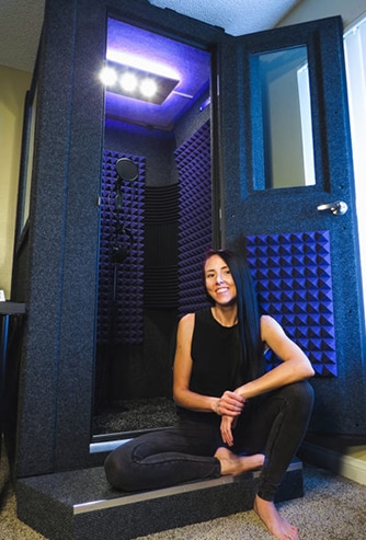 A woman sitting next to her WhisperRoom vocal booth