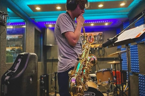 A saxophone player reading music inside of a WhisperRoom recording booth.