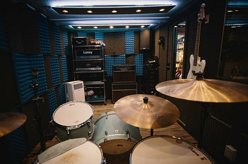 Drums, amps, and various other instruments inside of a WhisperRoom practice studio.