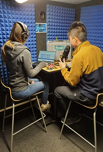 A young man and a young woman recording a podcast in the University of Pittsburgh's WhisperRoom vocal booth.
