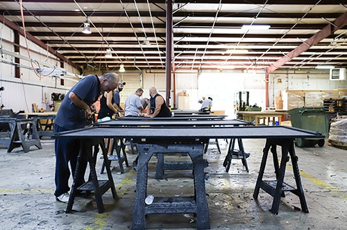 WhisperRoom's manufacturing plant with workers building components for soundproof booths