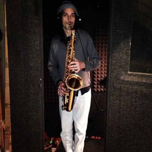 A man playing saxophone inside of his WhisperRoom practice booth
