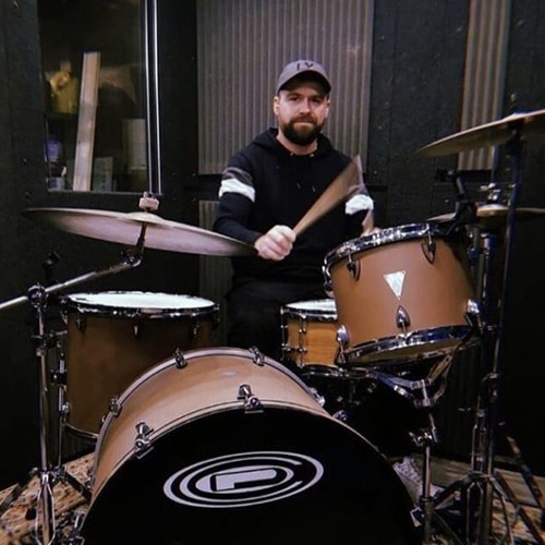 A man playing drums inside of his WhisperRoom drum booth