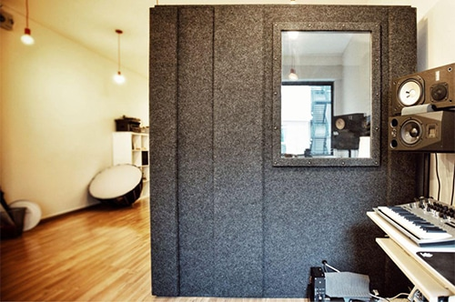 A WhisperRoom recording booth on a hardwood floor in a home recording studio