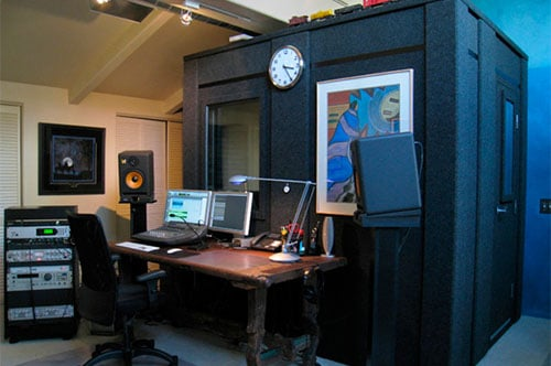 A recording booth with assorted audio gear inside of a home studio