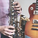 Man playing saxophone next to a guitar