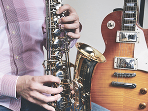 Man playing saxophone next to a guitar