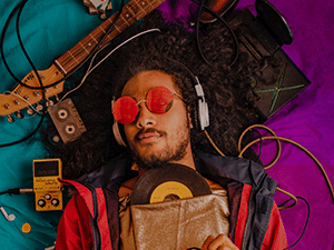 A man wearing headphone and listening to music with instruments around him
