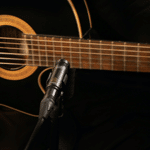 A black acoustic guitar and a microphone for recording