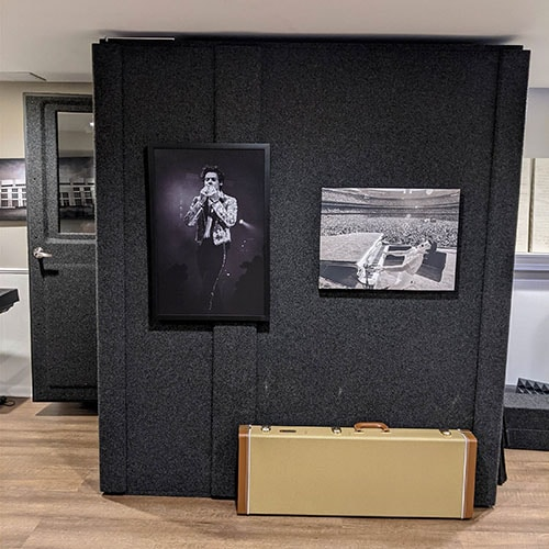 A WhisperRoom MDL 4872 S shown from the side with an open door inside of a home studio.