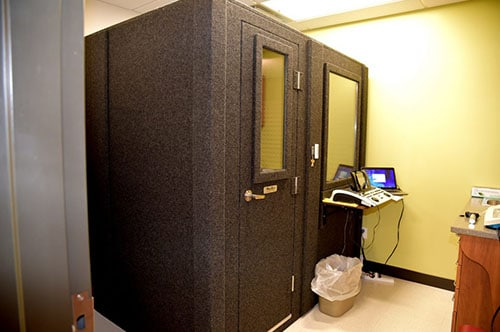 A WhisperRoom MDL 6084 S, a 5'x7' single-wall audiometric booth, is set up in an office for diagnostic hearing tests.