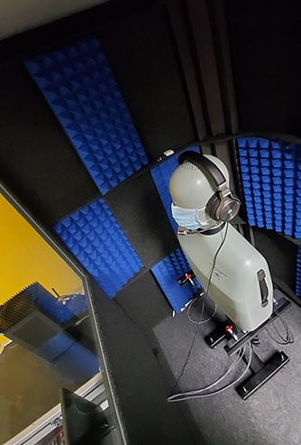 A testing dummy wearing headphones and a mask inside of a WhisperRoom MDL 4848 S.