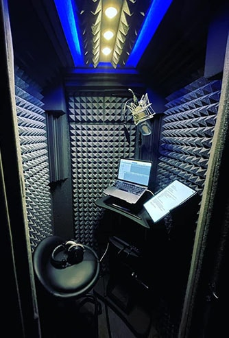 The interior of WhisperRoom's Voice Over Basic Package shown with a computer, microphone, headphones, and chair.