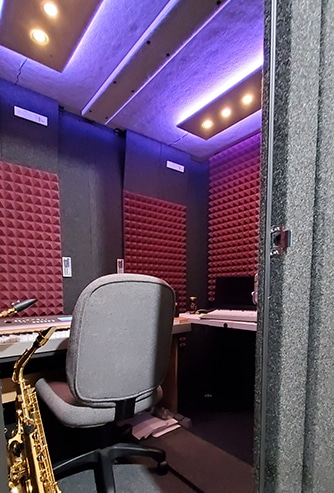 A saxophone, chair, and other instrumental gear inside of a WhisperRoom MDL 6084 S professional rehearsal booth.