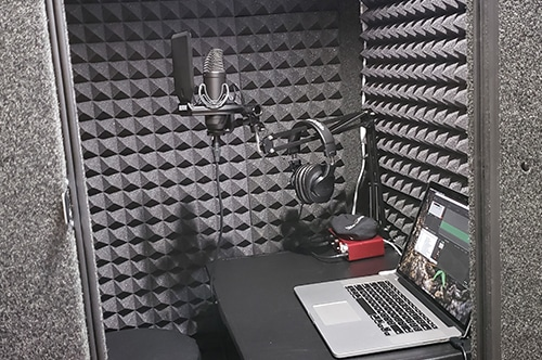 A microphone, laptop, interface, and other miscellaneous recording equipment inside of a WhisperRoom vocal booth.