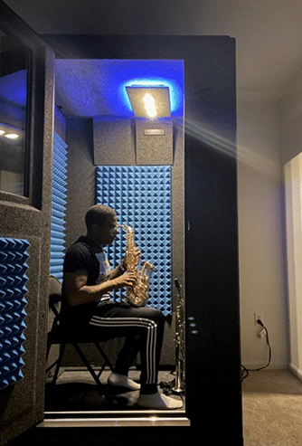 Musician Antonia Hart getting ready to play saxophone inside of his WhisperRoom sound booth.