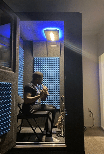 Musician Antonio Hart paying flute inside of his WhisperRoom sound isolation booth.