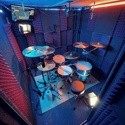 A full drum set inside of a WhisperRoom drum booth.