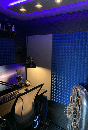 A recording setup and a tuba inside of a WhisperRoom sound isolation booth.