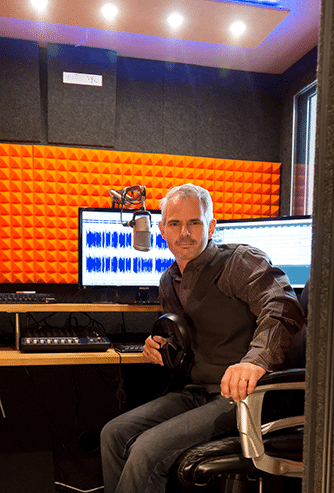 Jean-Marc Jihem sitting next to his computer inside of a WhisperRoom broadcasting booth.