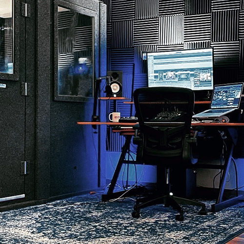 A recording desk with computers, speakers, a microphone, and chair set up in a studio next to a WhisperRoom.