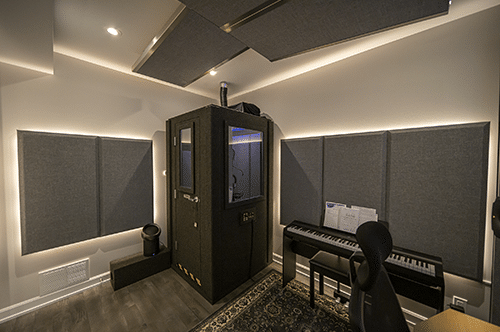 A WhisperRoom vocal booth in the corner of a production studio's room with several acoustic panels on the wall and ceiling.