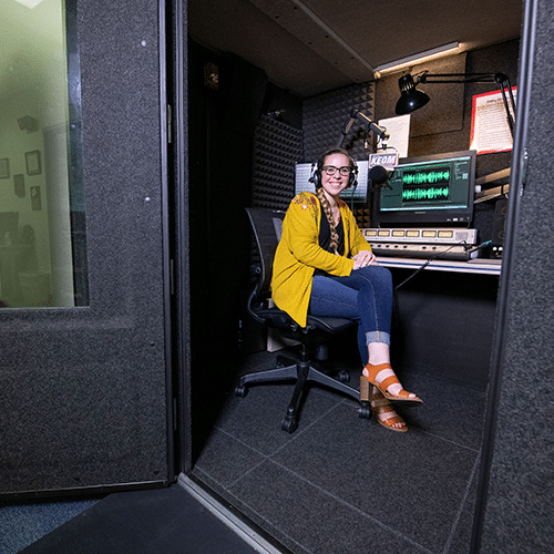 A student inside of KEOM's WhisperRoom broadcast booth.