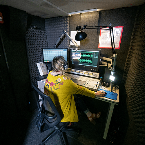 A student working on a podcast inside of KEOM's WhisperRoom broadcast booth.