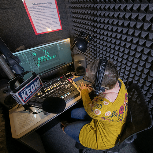 Podcast gear and a female student recording a podcast in KEOM's WhisperRoom.