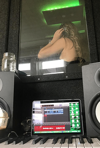 A woman singing inside of a WhisperRoom vocal booth