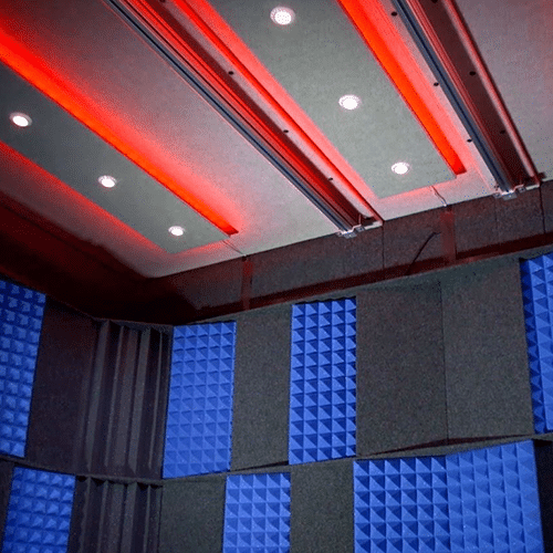 The interior of a WhisperRoom with red studio lights and the acoustic tuning package on the wall.