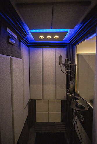 The inside of a WhisperRoom soundproof booth with acoustic panels on the wall and a condenser mic for recording.