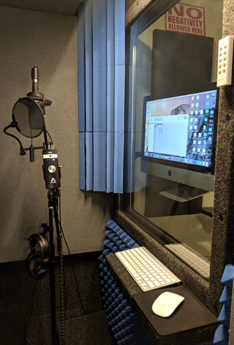 The inside of a WhisperRoom recording booth with a microphone, bass traps, and computer equipment.