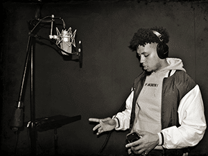 Young man wearing headphones prepares to record vocals into a condenser microphone